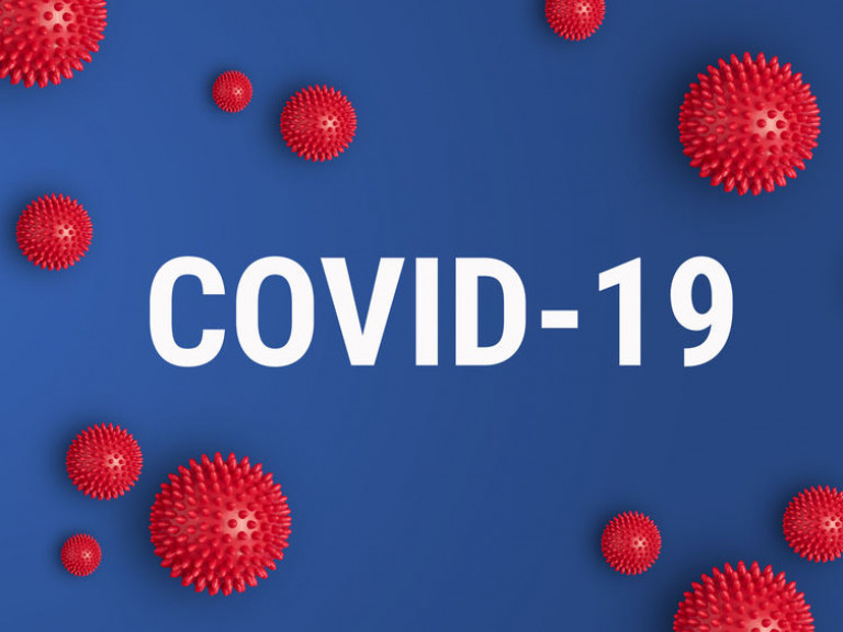 Inscription COVID-19 on blue background with red strain model of coronavirus